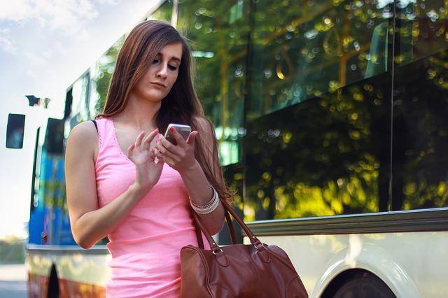 Žena jdoucí z autobusu s kabelkou